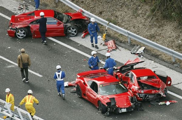 Police officers investigate wrecked luxury cars at the site of a traffic accident on the Chugoku Expressway in Shimonoseki