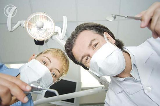 Dentist and assistant leaning down to work on patient