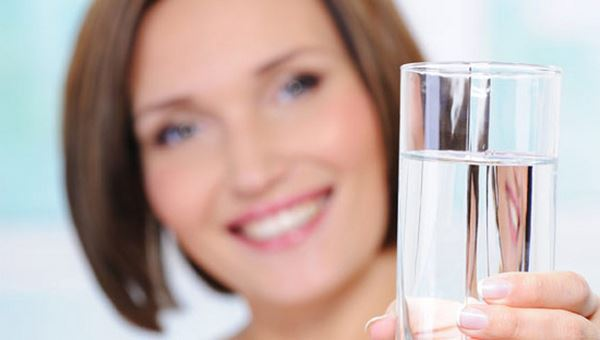 Woman holds glass of clean water